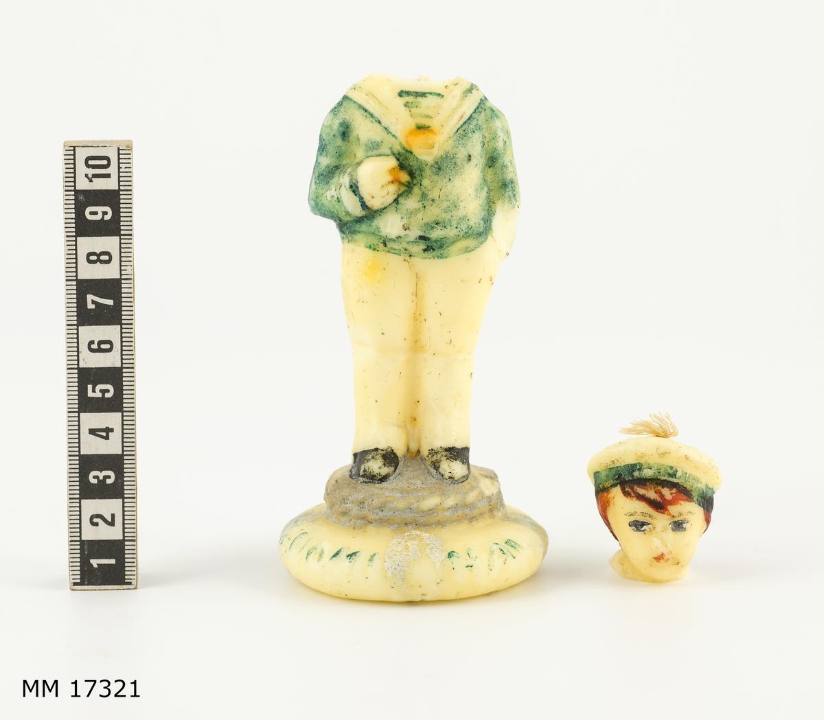 """Figur av stearin eller vax föreställande pojke iklädd sjömanskläder: rundmössa med turkost band och vitt kapell, turkos bussarong, skjorta med vit krage, vita byxor, svarta skor. Ena handen håller i en cigarett? den andra är nedstucken i byxfickan. Pojken står på en rundlagd tross. Längst ned en vit bottenplatta med relieftext= """"SUOMI NAVY"""". Genom figuren går en ljusveke som avslutas på mösskullen."""