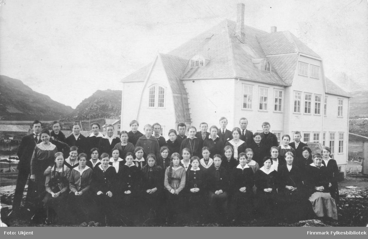 Et gruppeportrett av elever og lærere ved Øytun ungdomsskole. På bildet ser man flere unge gutter og jenter. Enkelte er kledd i samiske drakter. Jentene er kledd i kjoler, skjorter og skjørt. Enkelte har på seg smykker. Flere av jentene har flettet hår. Guttene er kledd i dress og slips. I bakgrunnen kan man se skolebygget, og bak den ser man et annet bygg. Helt til venstre kan man se en kai. Bildet tatt ca. 1920.