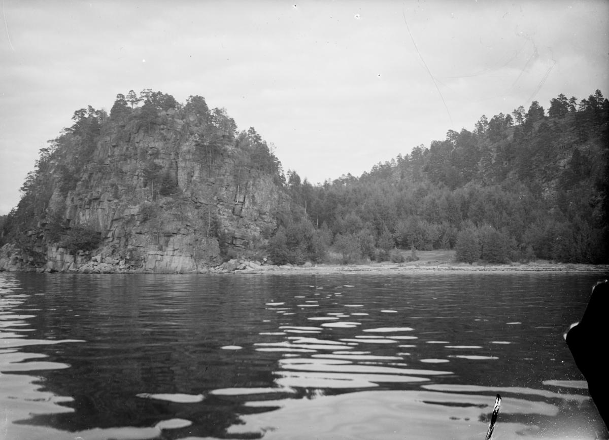 """Landskapsbilde av fjellknauser med skog, langs vannet..Tekst fra Teigens katalog: """"Svelviks Historie, Svelviks museum etc. se også: Drammens Tidende, se også: Hurum Bygdebok 4938"""""""