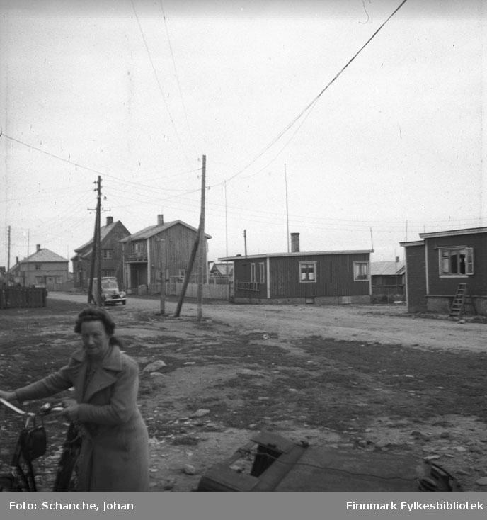 Damsveien i Vadsø. Tatt fra samme plas som fb.95066-003. En kvinne med sykkel på venstre hjørne av bildet. En bil  kjører langs grusveien. To bungalover til høyre på bildet, bungalovene hører til Torvald berg og familien Gandola.