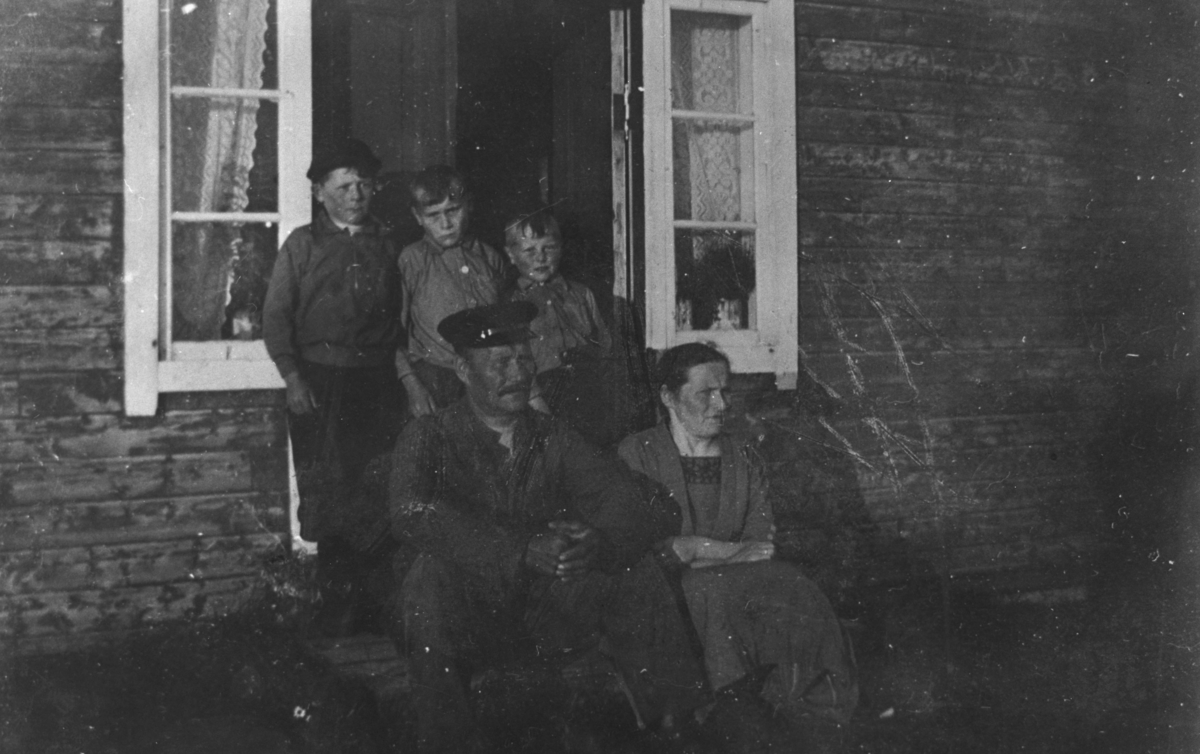 Familien Reisænen fotografert på trappa til huset sitt(?). Far Teodor Reisænen sitter med konen sin, Emma, på trappa og guttene (fra venstre) Magnus, Alf og Sverre står bak foreldrene. Bak guttene er dørroppningen til huset og lange, smale vinduer på hver side med gardiner og blomster på.