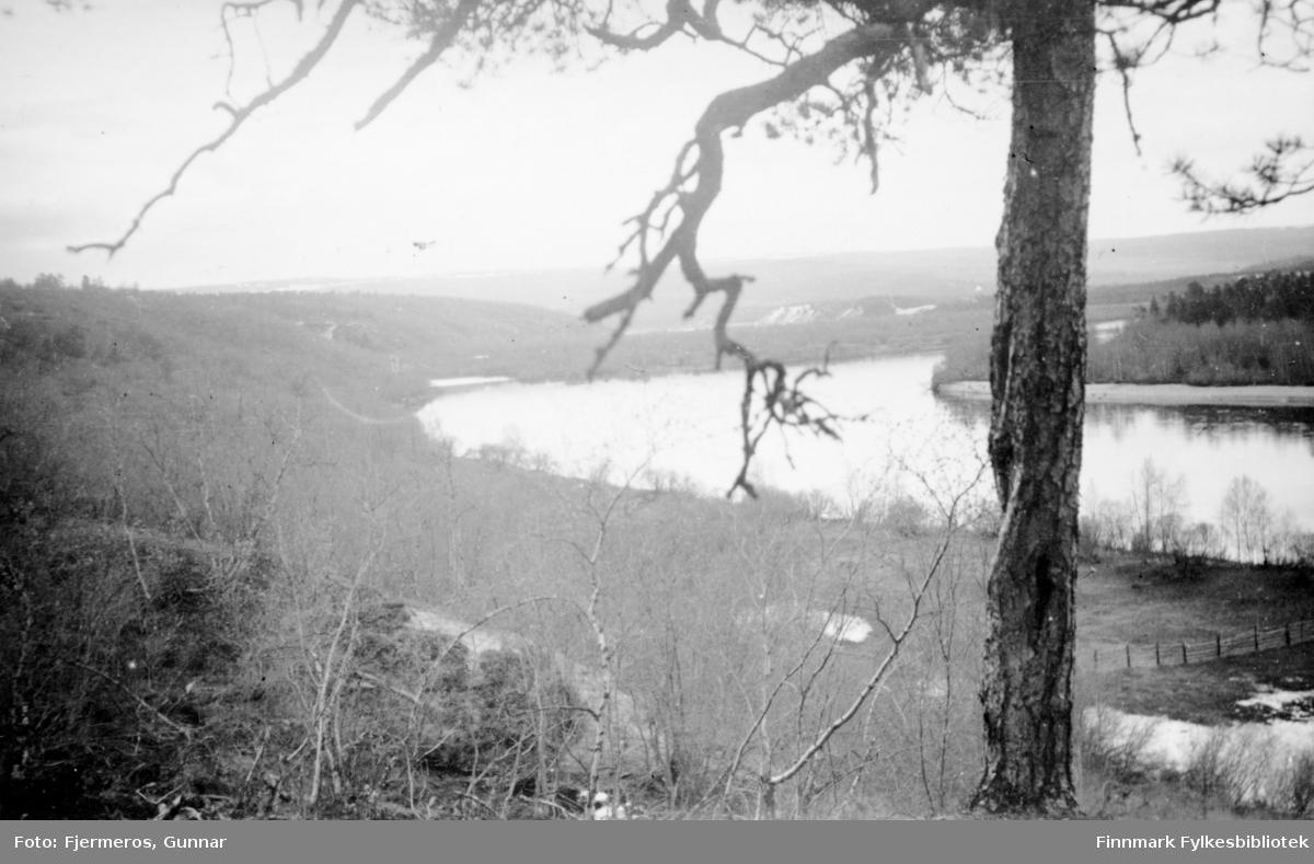 Jorrenjàrga i Karasjok kommune med elva Karasjohka i bakgrunnen. Et jorde med en liten hesje ses ved elvebredden nede til høyre. Bildet er tatt i mai 1946.