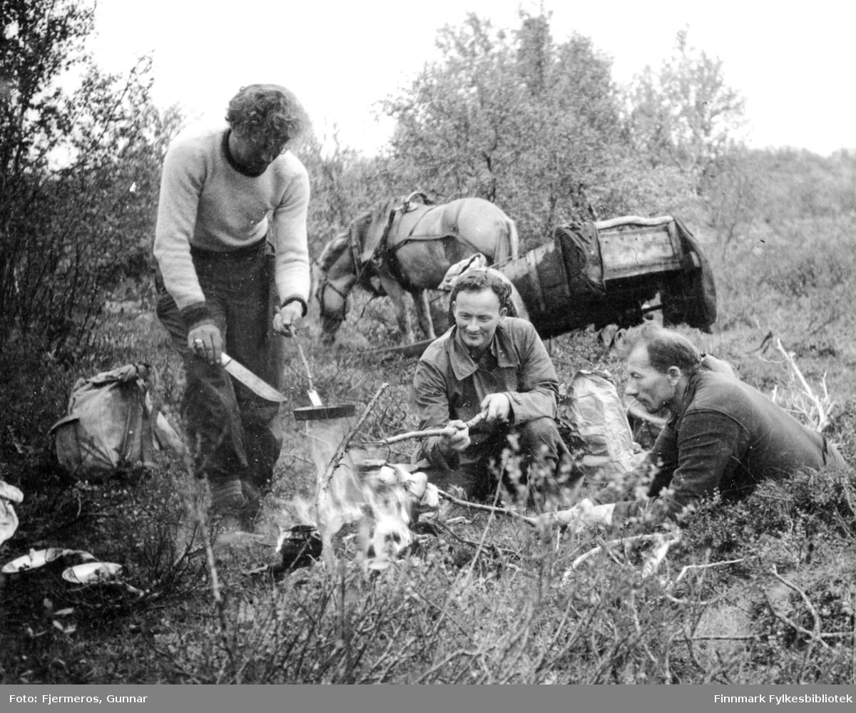 Tre personer rundt et leirbål på Finnmarksvidda under en tur til Suossjavri i Karasjok kommune i september 1946. Personene er ukjente.