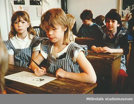 Barn som sitter i skolbänkar av äldre modell. Mölndals museum, 1990-tal.