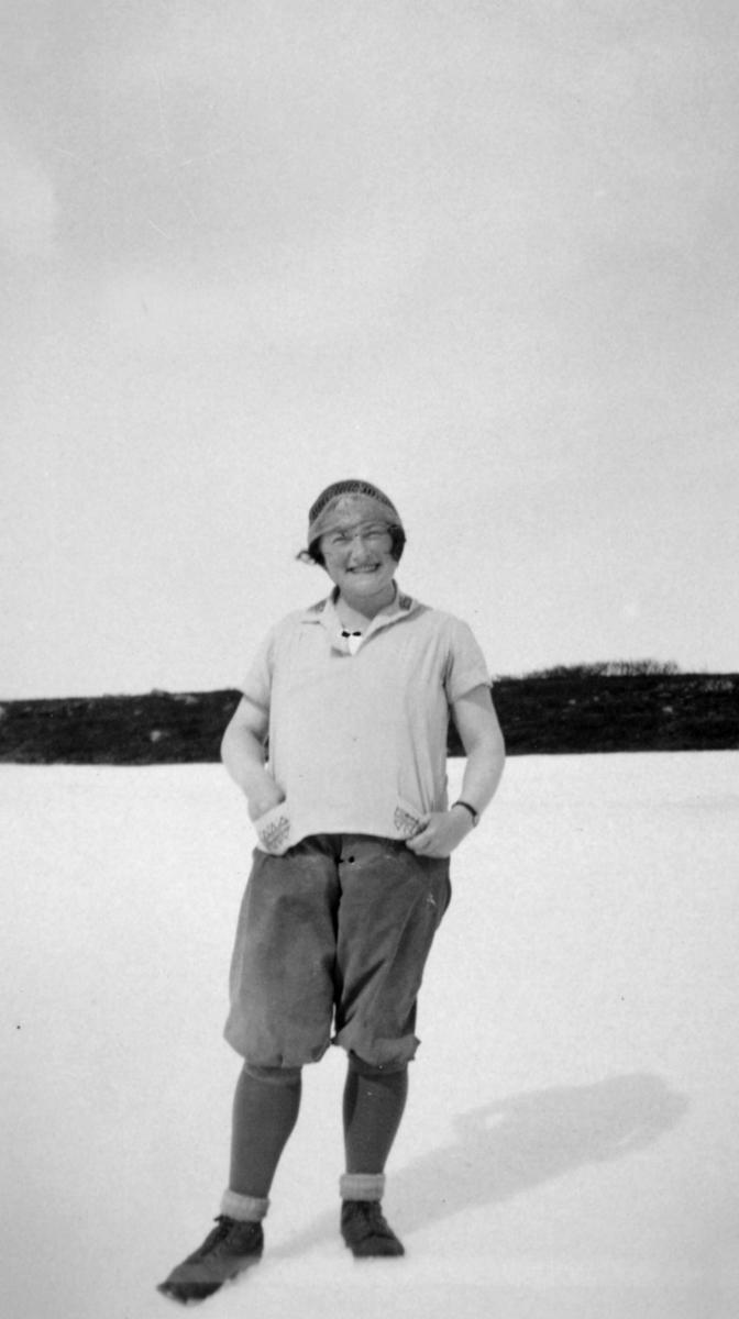Aslaug Wold poserer for et bilde. Hun er kledd i en kortermet skjorte og knickers. På hodet har hun et skjerf.