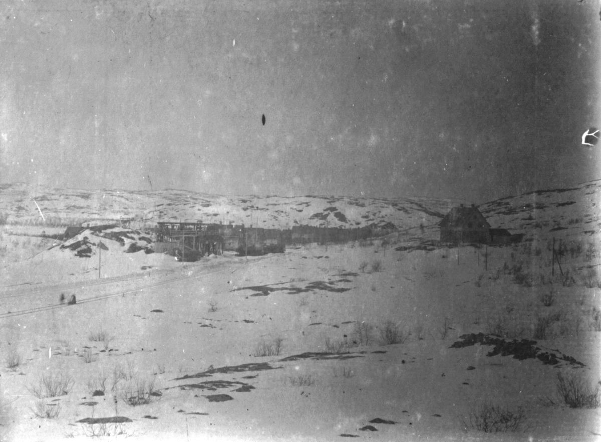 """Bilde er tatt ca 1910 fra Bjørnevatn og viser den sørligste delen av gruvebyen og er tatt i fra haugen som nu er borte, men der nyverkstedet ligger i dag. Broen (Luftbroen) som ble bygget senere går over jernbanen og veien til drifta, ca. der vi ser to mennesker på jernbanen. Bilde er tatt fra sør og mot nord. """"Vi ser på bilde 2 menn på jernbanetrasén, den ene sitter på en Drasin (sparkesykkel som var tilpasset jernbaneskinnene slik at du kunne bruke den som en spark nesten. Vi unger tyvlånte ofte slike til litt fart på jernbanen som egentlig var etc.""""... Trasén til venstre er gammelveien til gruva. Huset som er avbildet til høyre er Bjørnevatn første samvirkelag og ble da det første bygg på det vi kaller øversiden av jernbanen. Bla. familien Henrik Sannes bodde i dette huset, han kom fra Målselv. Bygget var også Posthus. (Se Samvirkehistorien) I bakgrunnen ser vi husene til gruvebyen og helt bak ligger Kjørstahaugen som er likedan i dag. Bildets dårlige kvalitet gjør at man ikke kan se """"Linbanen"""" til venstre, men man ser tydelig selve haugen.  (Bildeopplysninger av Kurt Røst, oktober 2010)."""