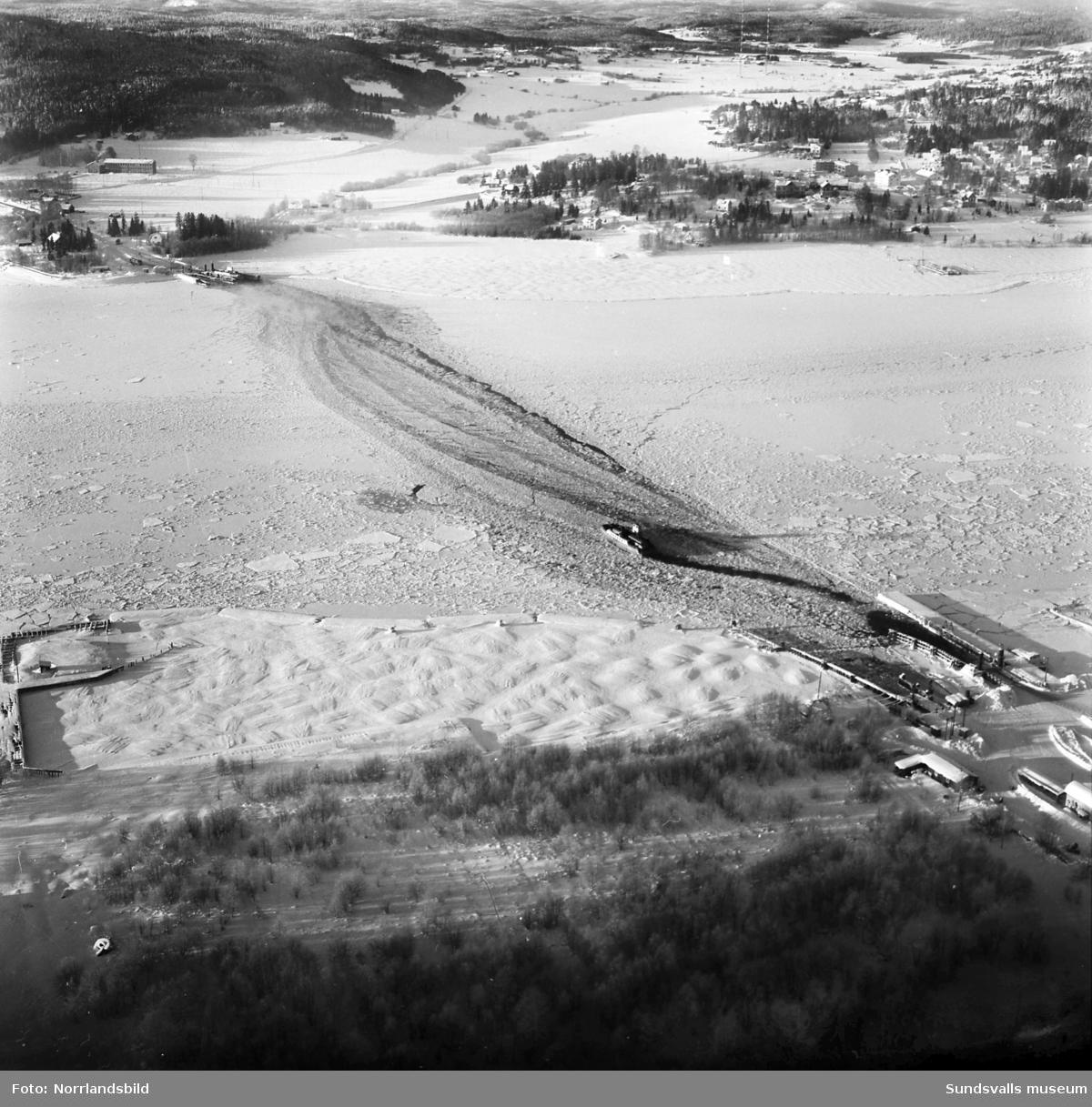 Flygfoto över Alnösundet med färjelägena på Alnö och i Fillan. Däremellan är Alnöfärjan på väg i isrännan.Till höger Johannedal och längre upp radiomasterna i jordbrukslandskapet där numera (2015) Birsta köpcentrum breder ut sig.