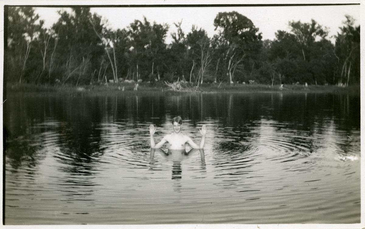 Bildet viser en ung mann som bader i en innsjø. Personen på bildet oppgis å være Ingvald Brekken. Dette er et postkort.