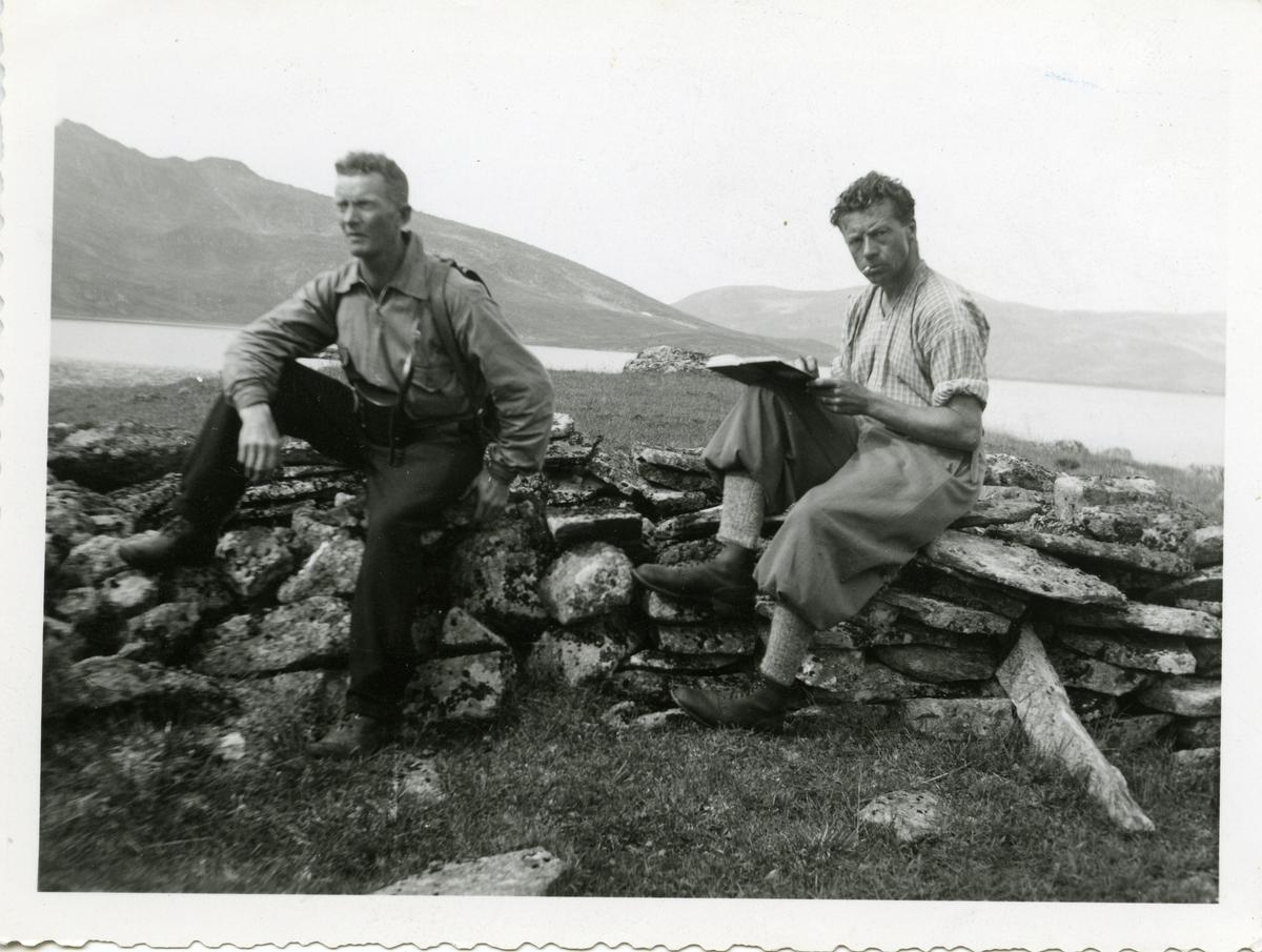 To menn sitter på et steingjerde ved en sjø. Mennene er iført turklær.