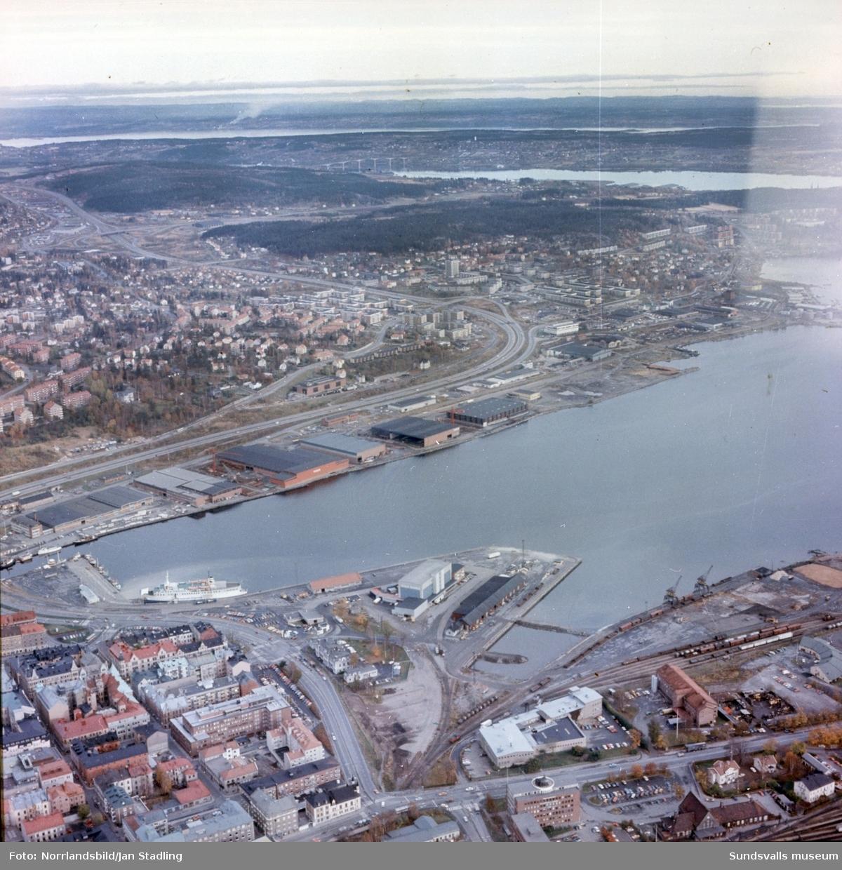 Flygfoto i färg från 1977 över Sundsvalls hamn. Bilden är tagen norrut och längst ner till höger syns järnvägsstationen. Norra kajen, Haga, Skönsberg motorvägen och Alnöbron syns högre upp i bild.