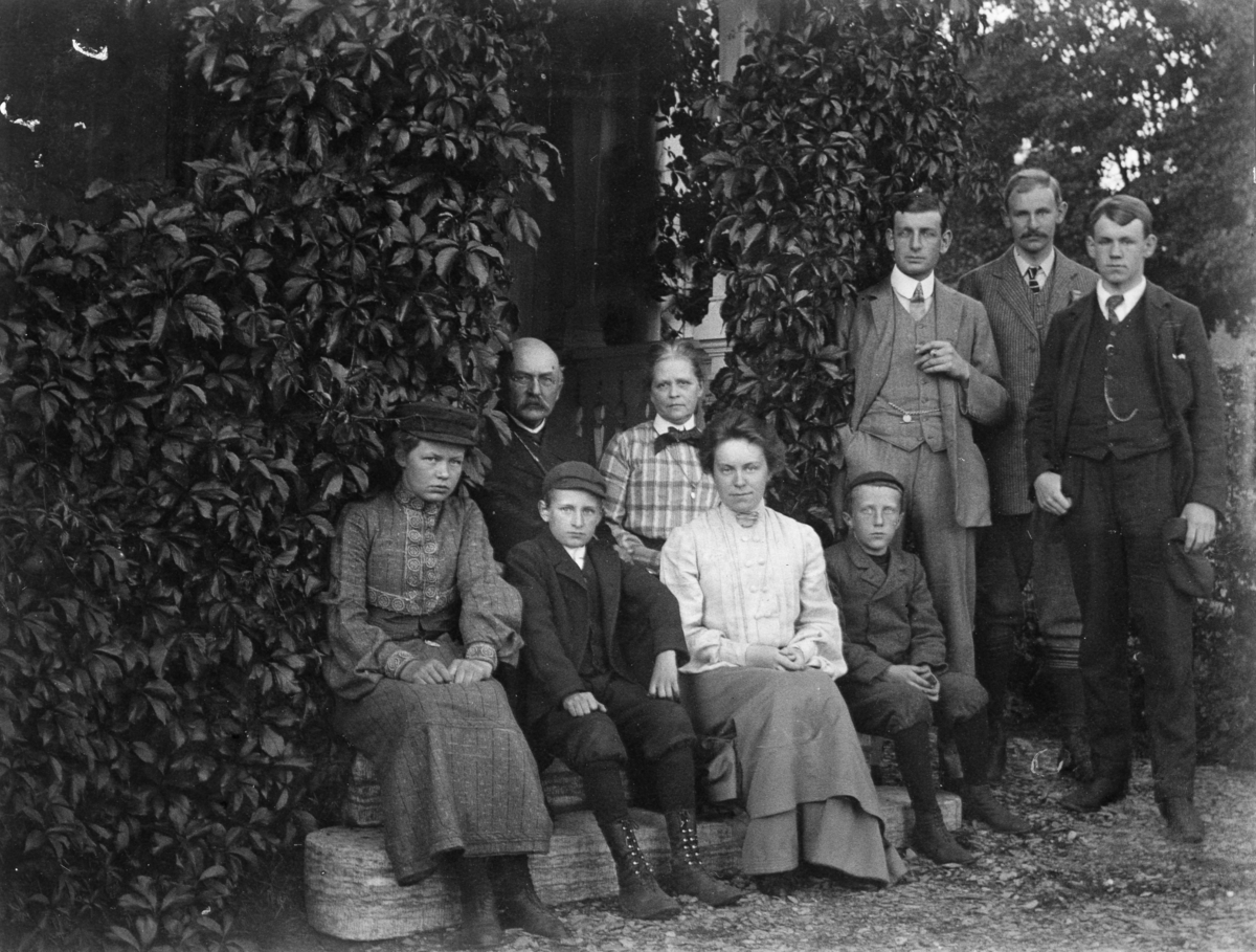 Fotosamling etter Cappelen. Utendørs familieportrett. Fra venstre: M.K., G.K., M.Od., E.C.K., C.K. Gutten som sitter foran Gunnar Knudsen er Rolf Knudsen og kvinnen som sitter ved Rolfs venstre side er Louise (Lulli) Knudsen. På Rolfs høyre side sitter Margit (Maggit).