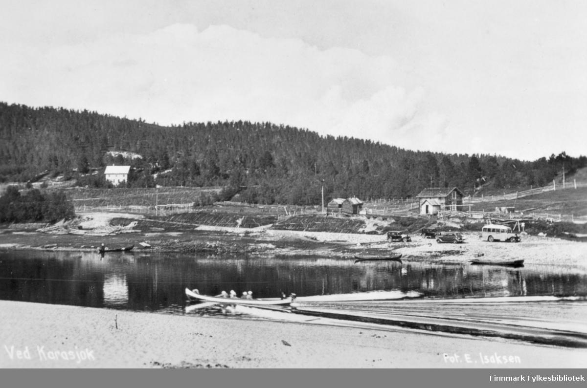 Et fotografi av Karasjok i form av et postkort. Man kan se at folk ror i båter på vannet. I bakgrunnen kan man se flere biler parkert nær vannkanten. En av bilene ser ut til å være en buss. Bildet trolig tatt i løpet av siste halvdel av 1900-tallet.