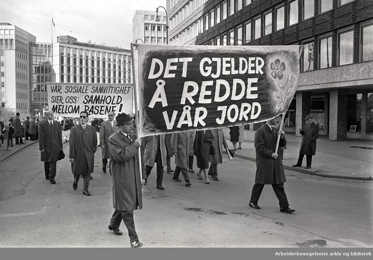 1. mai 1964 i Oslo.Demonstrasjonstoget gjennom Borggården.Parole: Det gjelder å redde vår jord.Parole: Vår sosiale samvittighet sier oss: .Samhold mellom rasene!