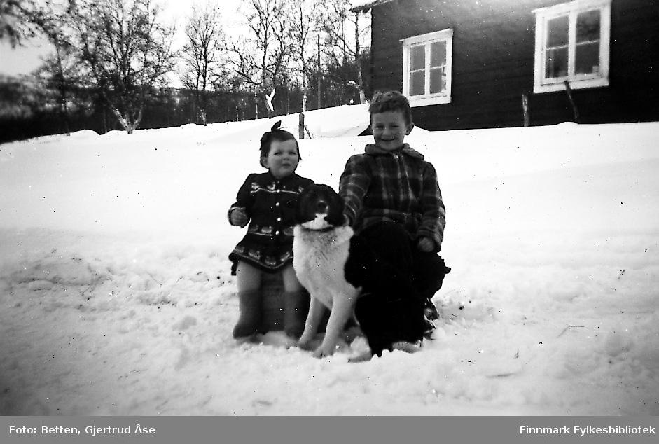 To barn, en jente og en gutt, sitter på en trekasse på vegkanten ved et bolighus. Mellom dem sitter en sort/hvit hund. Den lille piken på ca 2 år heter Svanhild Johansen og gutten på 6 år Bjørn Ottar Betten. Landskapet er dekt av snø. Bakerst står huset.