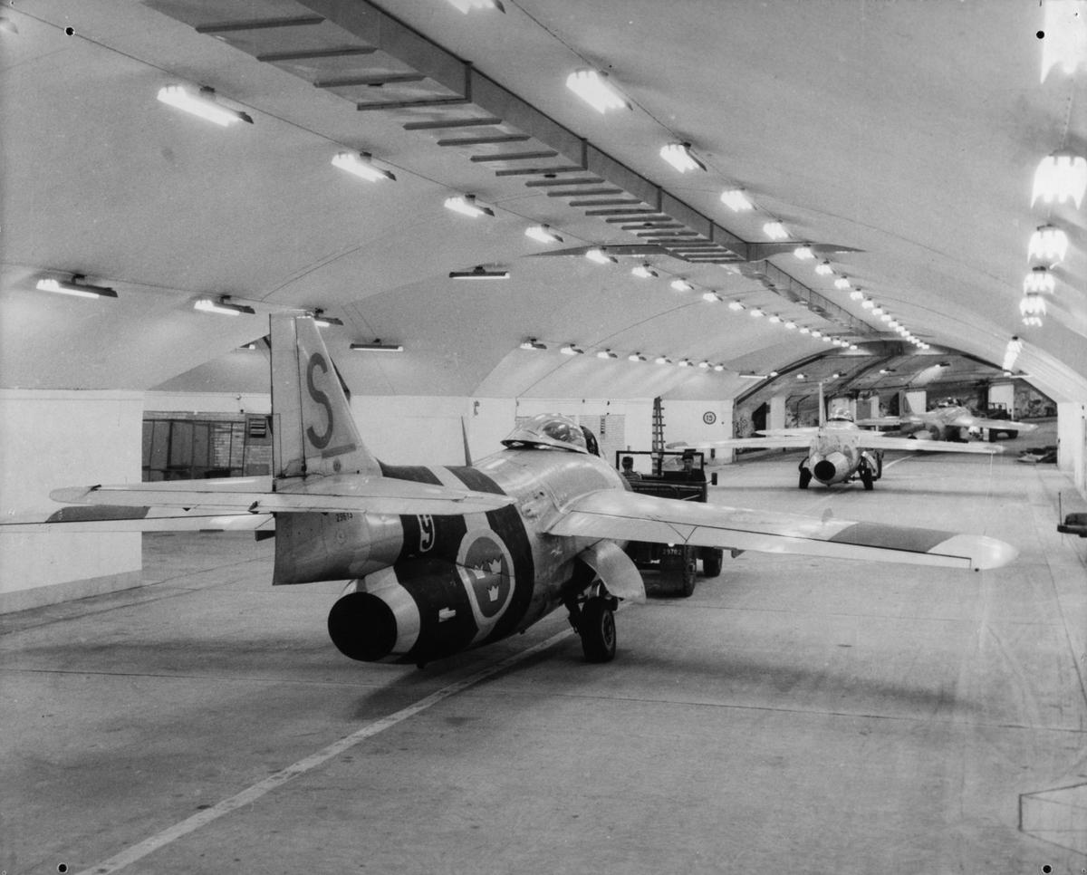 Tre stycken flygplan J 29 Tunnan bogseras i hangar på F 9 Säve.