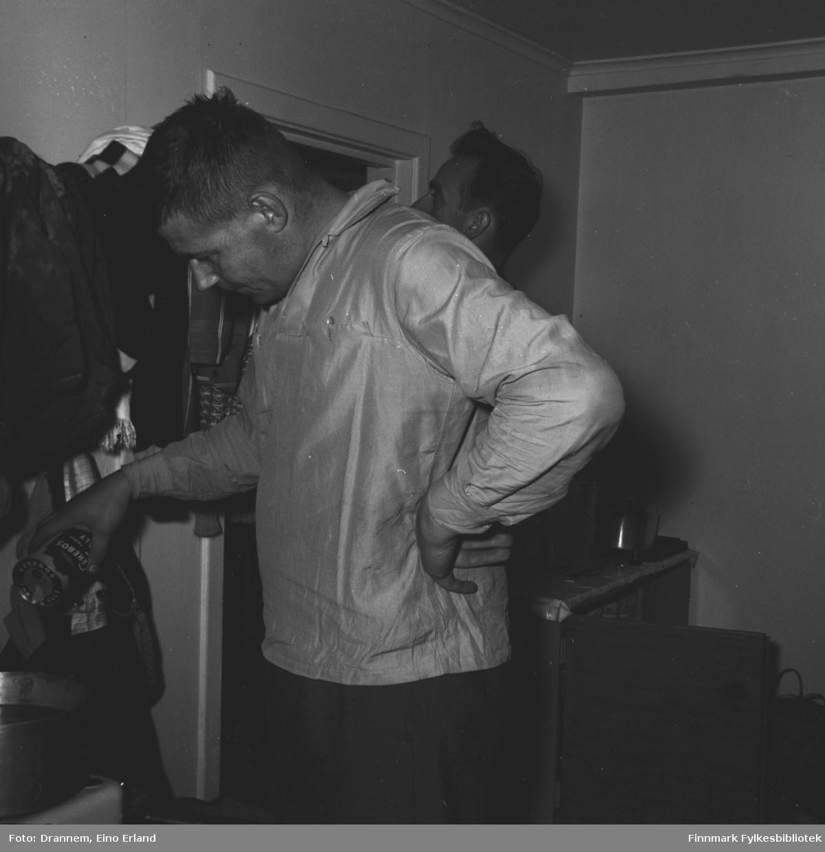 To menn i kjøkkenet, den andre lager mat