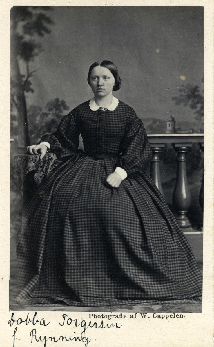 Helfigurportrett av kvinne. Hun er kledd i rutete, fotsid kjole med hvite mansjetter og krage med en nål/sølje i halsen. Bildet er tatt i et fotostudio, og hun sitter foran et gjerde.