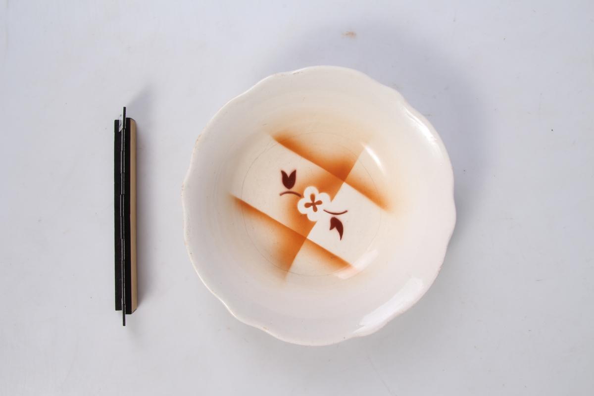 Rund skål med bølgete kant og blomsterdekor.