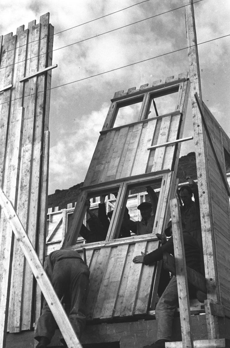 Arbeidere reiser et veggelement på et bygg i Honningsvåg like etter andre verdenskrig.  Ola Hanche-Olsen som har tatt bildene er født 13. mars 1920 i Borre, død 11. februar 1998 i Gjettum. Han var arkitekt og barnebokforfatter. Han hadde artium fra 1939, arkitekteksamen fra NTH 1946 og arbeidet deretter ved Finnmarkskontoret 1946–48 før han etablerte egen arkitektpraksis. Han debuterte som barnebokforfatter i 1974 med lettlestboka Knut og sjørøverne, og skrev i alt 12 bøker. Han var XU-agent 1944-45, og var også en aktiv fjellklatrer og friluftsmann. Ola var gift med Solveig Hanche-Olsen (f. Falkenberg); de fikk 3 barn, blant dem matematikeren Harald Hanche-Olsen.  Arkitektene Solveig og Ola Hanche-Olsen arbeidet ved Brente Steders Reguleringskontor i 1946. Hovedadministrasjon for gjenreisning av Nord-Troms og Finnmark ble lagt til Harstad og fikk navnet Finnmark kontoret. Landsdelen Nord-Troms og Finnmark blev oppdelt i syv distrikt med hver sin administrasjon. Honningsvåg, distrikt IV, skulle betjene Nordkapp, Lebesby, Porsanger og Karasjok kommune