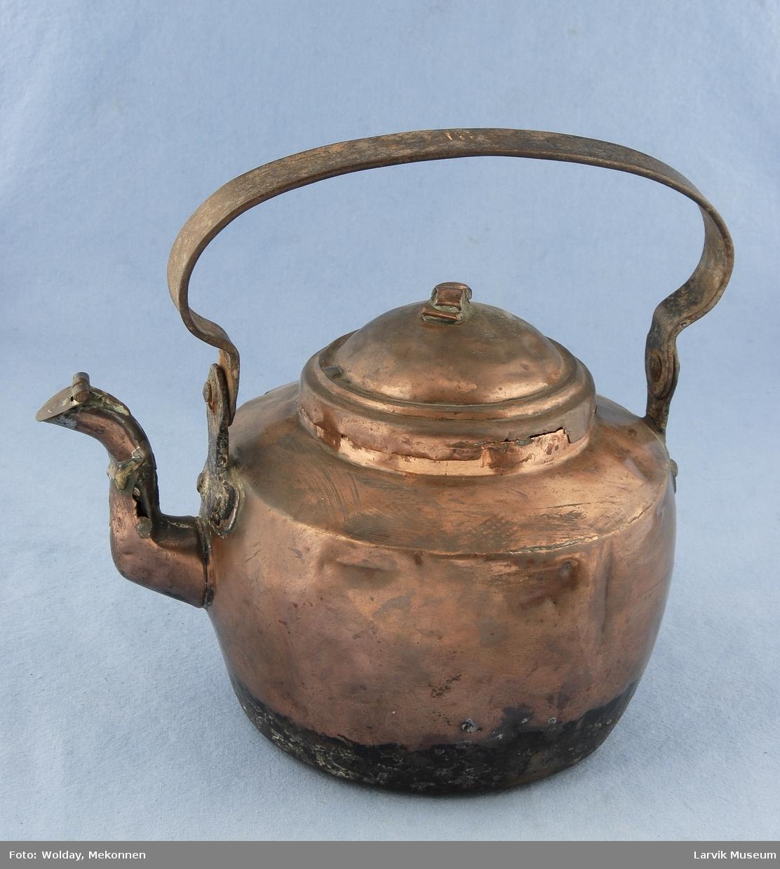 Form: vert.kant rundt åpning. hank av jern, festet til  jernbeslag som er festet til kj. med kobberstifter tut med lokk. krøllformet toppknott.