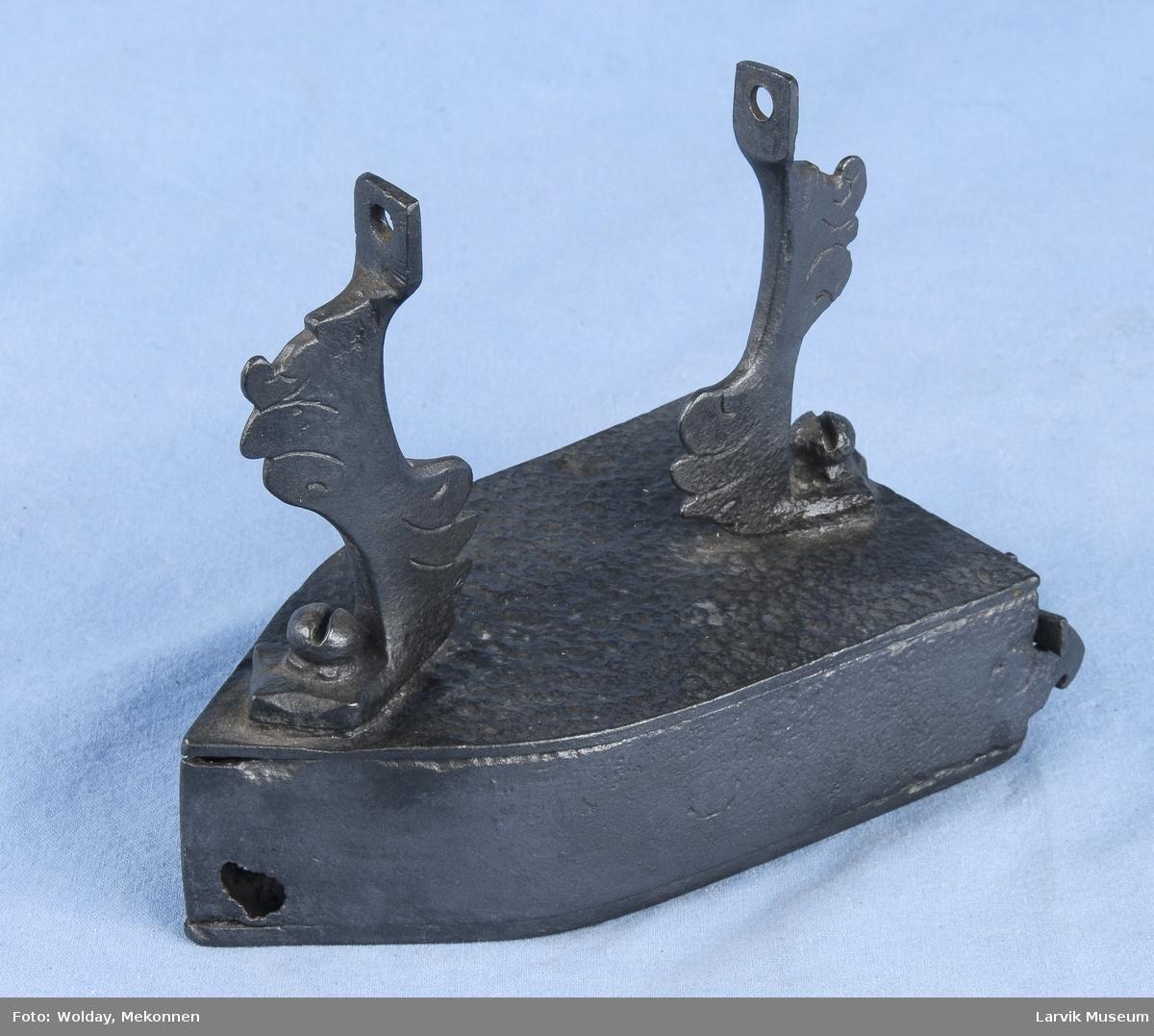 Form: sider,topp og bunn naglet sammen. dør på bakside hengslet med lukkemekanisme.på bunnen inni s-formet jernstykke. det manglende håndtak bæres av to ornamenterte støtter fastskrudd til jernet. 1 hull foran på hver side.