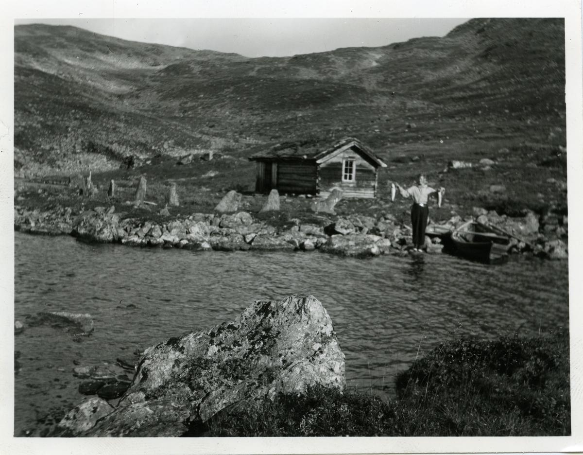 En mann avbildet foran en hytte ved et vann, og  med to fisker i hendene.