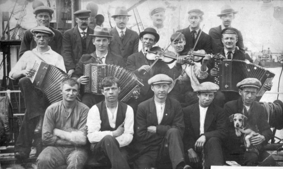En gruppe menn poserer for fotografen på det som kan se ut som et båtdekk. Flere av dem har instrumenter i hendene. Bildet kan være tatt i Kvalsund kommune før evakueringa.