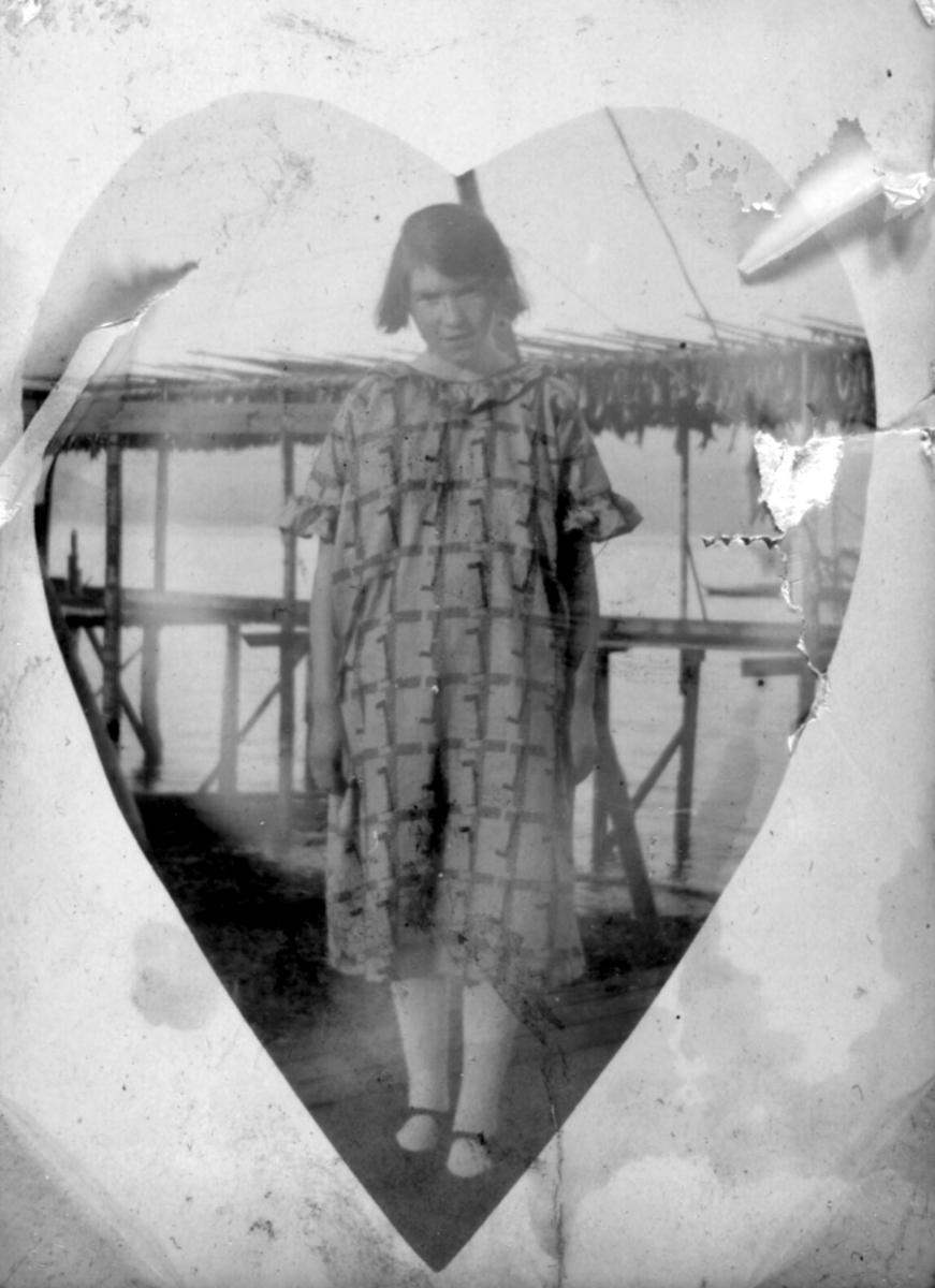 En ukjent jente fotografert på kaia med en fiskehjelle i bakgrunnen. Bildet er muligens tatt i Kvalsund kommune før evakueringa.