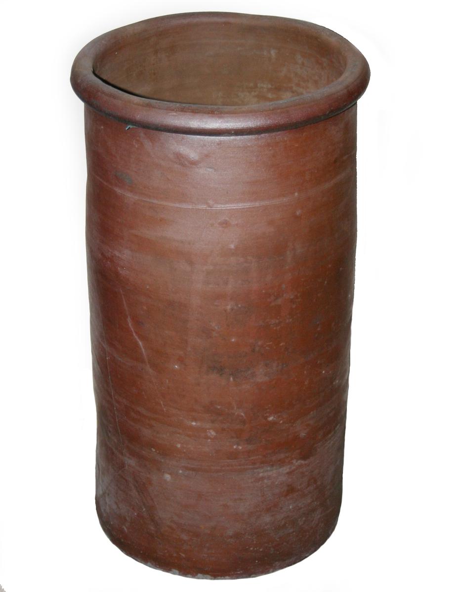 Smørdunk.  Stentøy, mørk rødbrun overflate.  Furu lokk.  Saltglasert.  Høy sylinderformet smørdunk med rundet brem. Flatt lokk med en tverrligger og en innskjæring ved tverrliggerens kar.