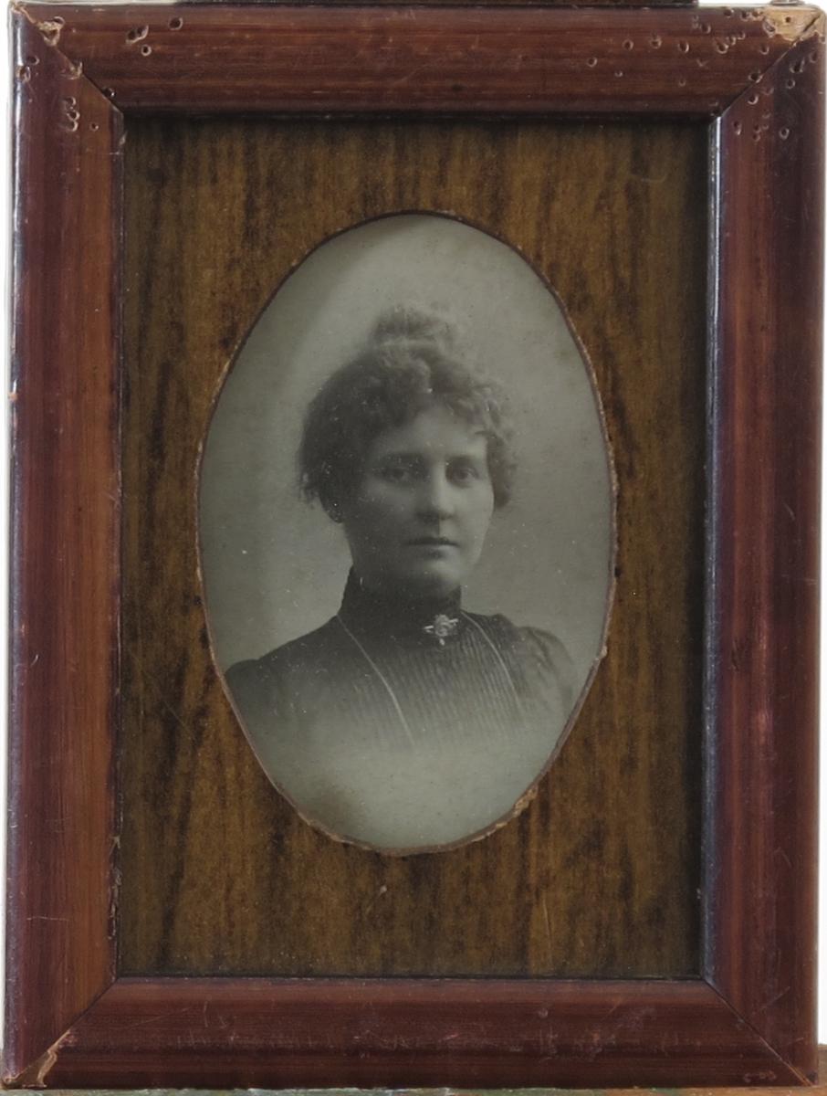 Fotografiet forestiller ung dame, håret oppsatt i topp, svart kjole med pliser,  høy hals. Kjede og nål på halsen. Forestiller Ragnhild Johnsen Langemyr, som hadde forretning i Nygt. Arendal.