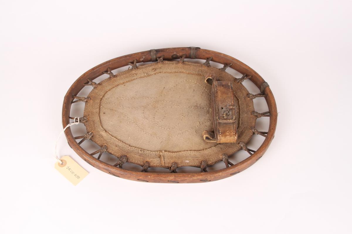 En enkelt rammetruge i tre med grov seilduk som fotstegplate. Seilduken er festet til rammen med lærremmer. Rammetrugen har en tårem i lær, med feste for bakrem.