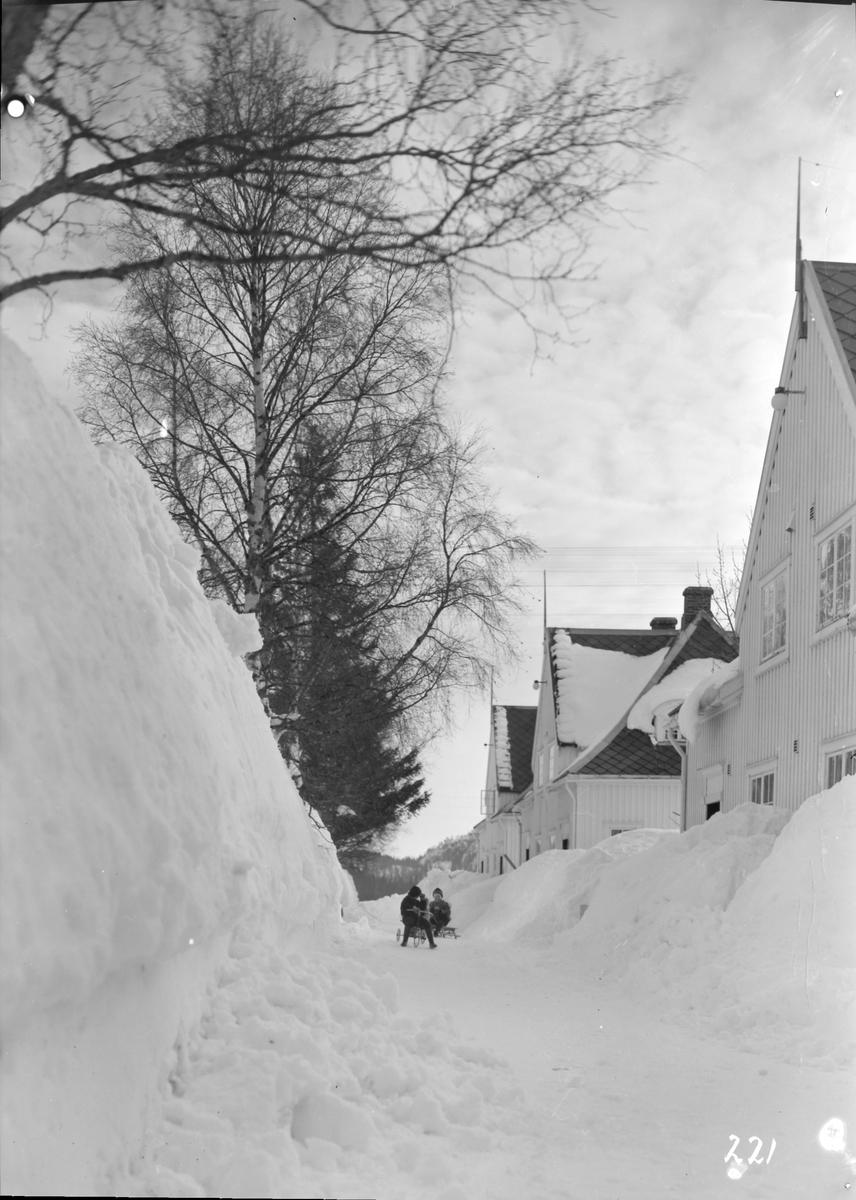 Torvet på Bjørnli. Mye snø, formannsboliger, barn leker.