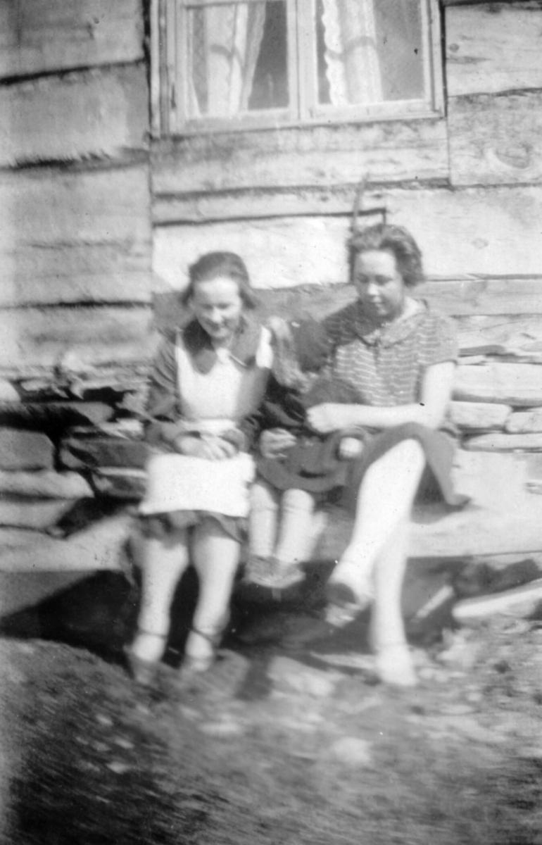 To ukjente kvinner sitter utenfor et hus. Sted og personer er ukjent, men bildet er muligens tatt i Kvalsund kommune.