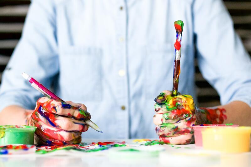 Bildet viser en mann som maler og tegner, med masse malingssøl på hendene (Foto/Photo)