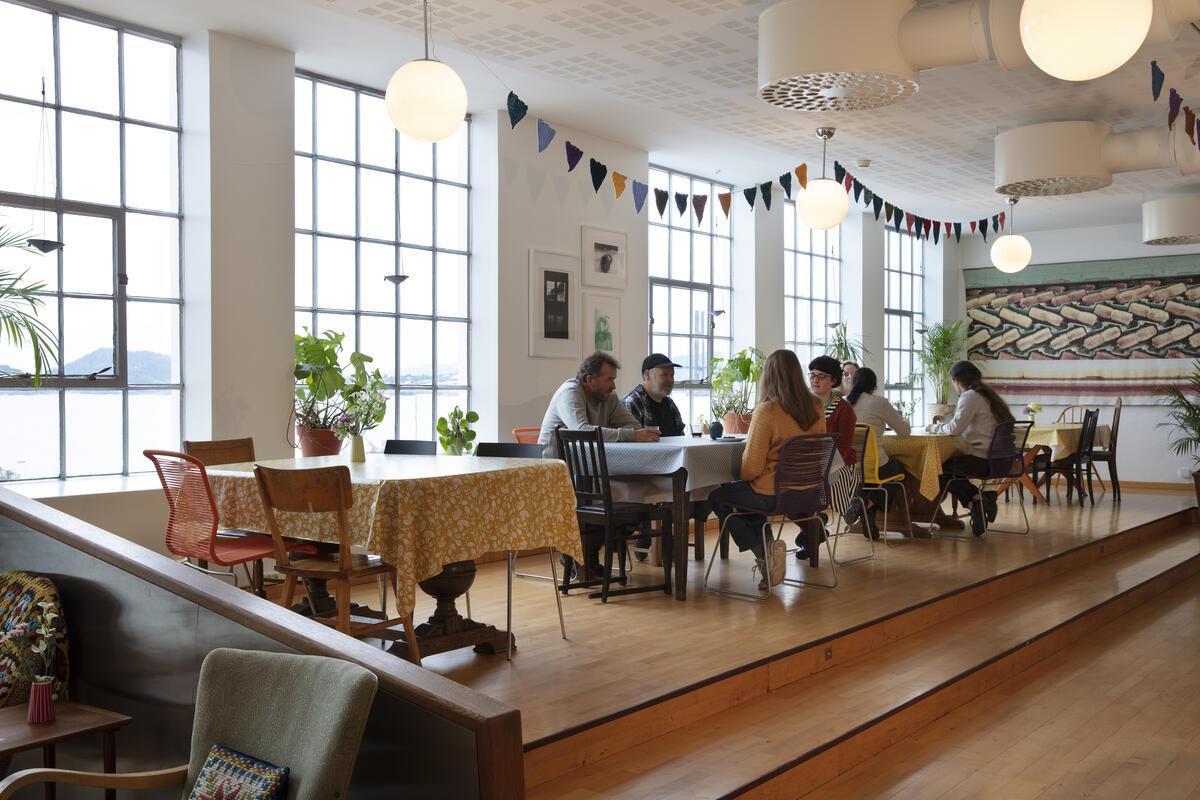 kafélokale med gjestar, stolar og bord, store fabrikkvindauge (Foto/Photo)