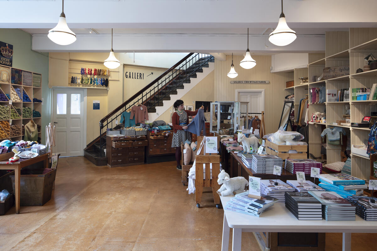 Butikklokale med bøker og tekstilar, kvinne ser på plagg (Foto/Photo)