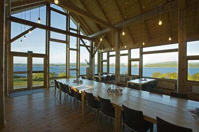 interiør med langbord, vindauge med utsikt over kystlandskap. Foto/Photo