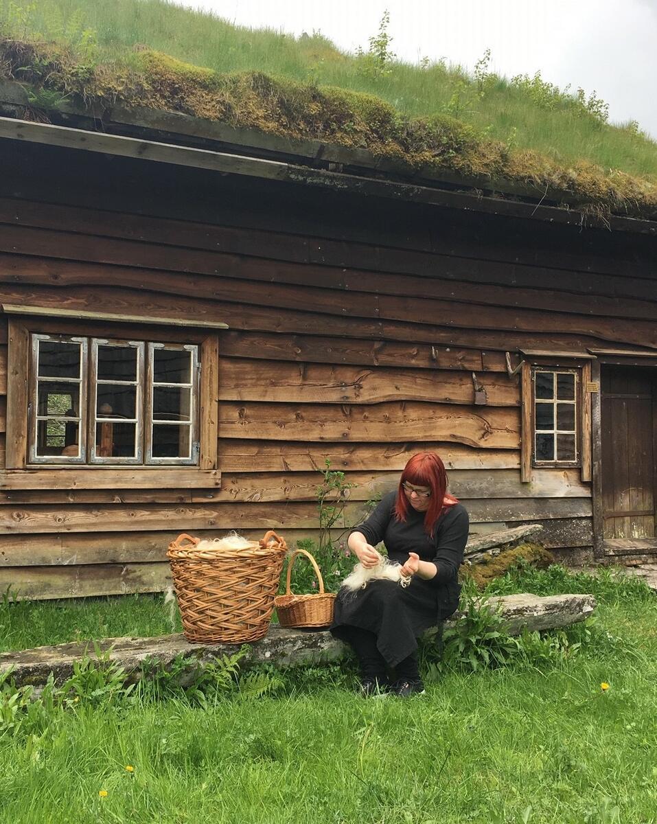 kvinne arbeider med ull utanfor gammalt trehus (Foto/Photo)