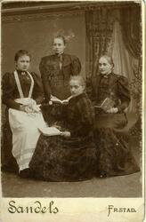 Gruppeportrett av fire unge kvinner. Bak på bildet har Arne
