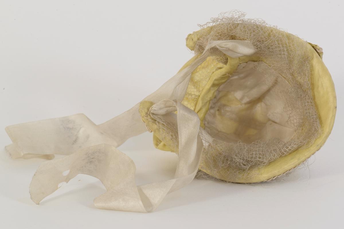 Dukkekyse i (oppr) gul silke med pyntebånd. Avstivet og pyntet med tyllkant og bånd. Foret med silke. Knytebånd i silke.