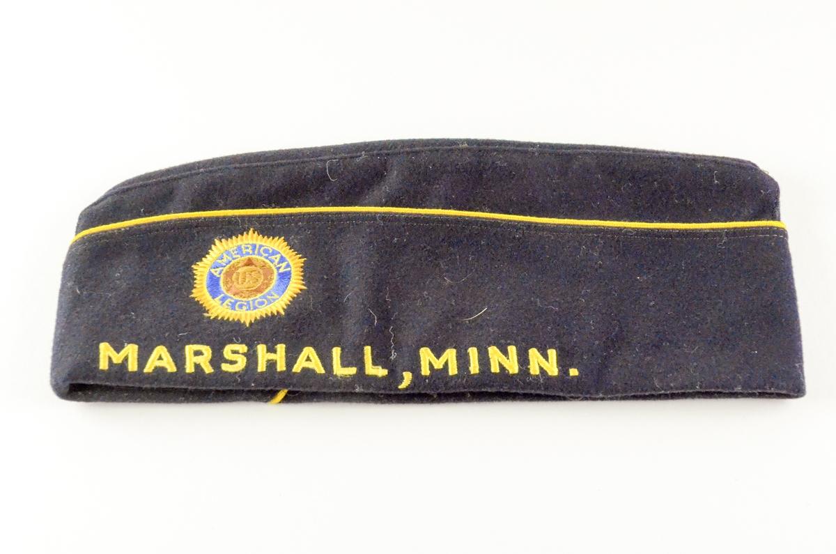 Båtlue tilhørende marineuniform. Mørk blå med gule render. Sydd med gult langs kanten: 113 MARSHALL, MINN. Emblem i front: stilisert sol med gult ytterst, lyst blått ibrodert American Legion, brunlig kjerne ibrodert U.S.