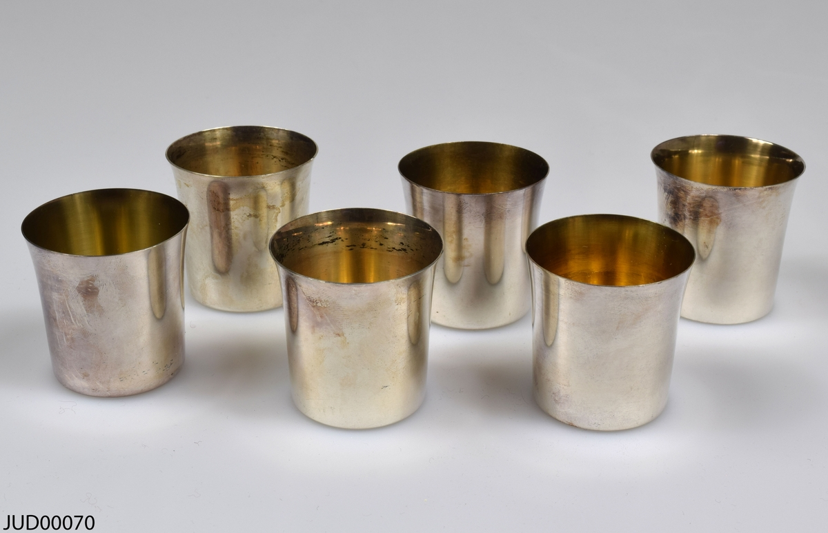 6 stycken små, enkla bägare utan fot, tillverkade av silver. Insidan av bägarna har en lätt förgyllning. Alla sex bägarna har tydliga stämplar i botten i följande ordning: Namnstämpel, Ortsmärke, två kontrollstämplar, Årsstämpel.  1: GAB, St. Erik, kattfot, silver S, S9 2: GAB, St. Erik, kattfot, silver S, P9 3: K & EC, St. Erik, kattfot, silver S, R9 4: K & EC, St. Erik, kattfot, silver S, Q9 5: K & EC, St. Erik, kattfot, silver S, Q9 6: GAB, St. Erik, kattfot, silver S, P9