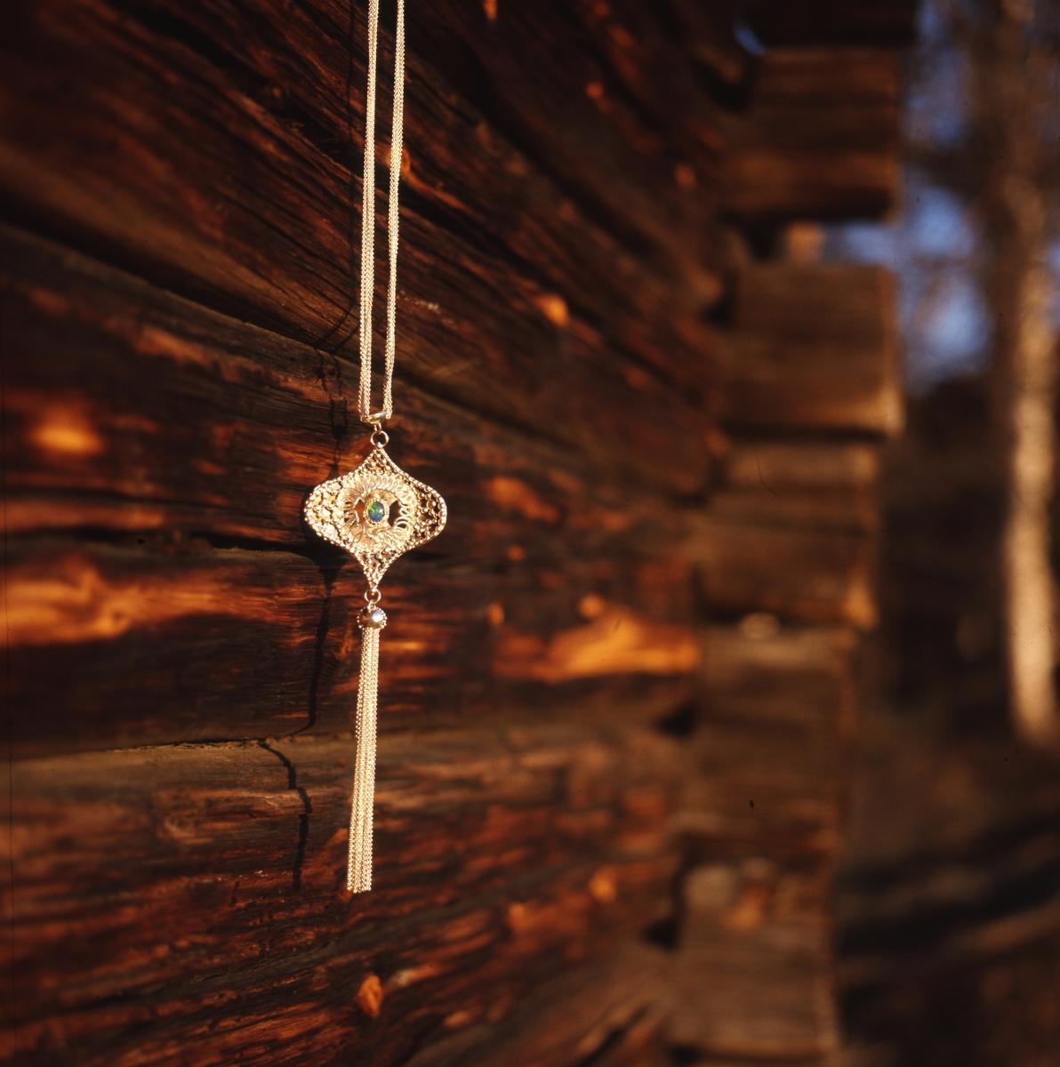 Silversmycke av Rosa Taikon avfotograferat mot timmervägg.