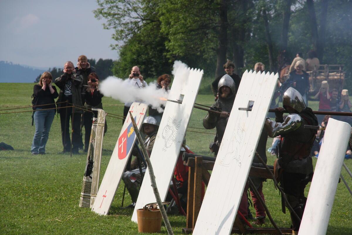 Menn kledd i middelalderrustninger gjemmer seg bak trepalisader med hull til løpet på håndholdte kanoner. Den ene kanonen har akkurat avfyrt, så røyken tyter ut av åpningen i palisaden. (Foto/Photo)