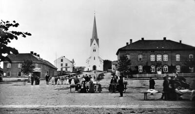 """Svart-hvitt fot som viser et torg med handelsboder og torgkoner i """"gammeldagse"""" klær, et hus i hver bildekant og Hamar domkirke bakerst i midten.. Foto/Photo"""