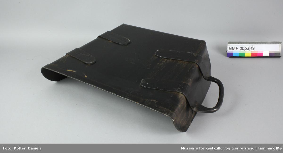 Skuffa er laget av svart lakket metall og er forsterket ved kanten. Håndtakene er naglet fast på undersiden. Skuffa er trapesformet. I bakkanten er det preget inn bokstavene SF for Sivilforsvar.