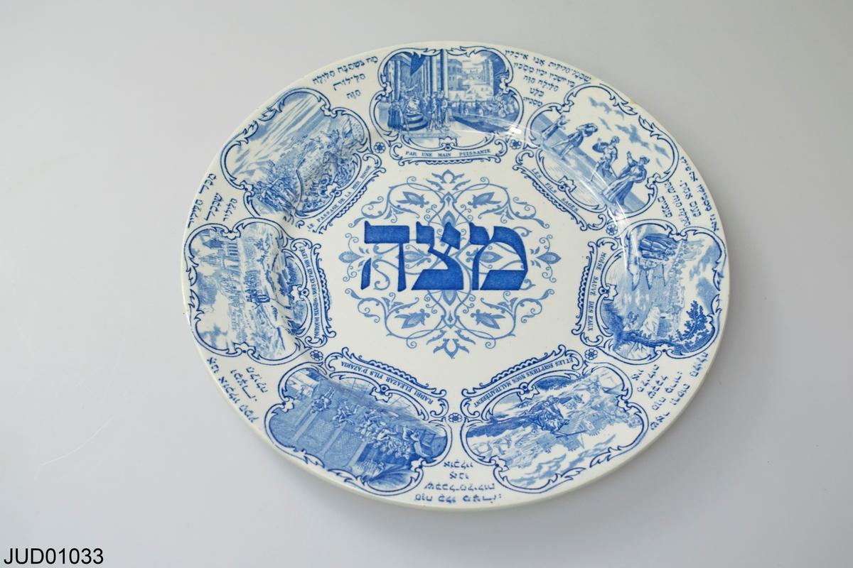 """Rund tallrik i porslin med blått tryck. Text """"matsa"""" på hebreiska och scener ur Amsterdamhaggadan."""