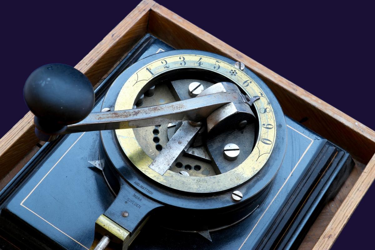 Svart upphöjd platta i metall med målade guldlinjer. Rund metallbricka i svart med mässingsdetalj högst upp. Siffror från 1-0 ingraverade längs med rundeln med spak för att välja siffrorna och perforera. En av maskinerna ligger i en trälåda med huva.