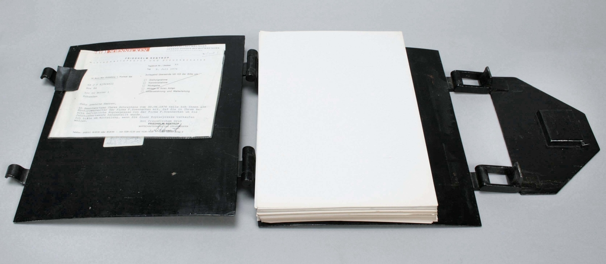 Kopiepress av svartlackerade stålplåtar, med förgylld ram-dekor i form av dubbla linjer. Tryckmekanism i form av hävarmsprincipen. Kopiebrev av papper i pressen. Märkt: F. Soennecken Berlin-Bonn-Leipzig, Nr 2 / Kopierpresse  Se även kopieböcker, BM 80248 samt BM 80255, hur resultatet blir med en kopiepress.  Funktion: För kopiering av brev skrivna med bläck  Familjeföretaget AB J.F. Björsell startades 1888 i Borås av Johan Fredrik Björsell och var verksamt inom kontorsvaru- och tryckeribranschen. Johan Fredrik Björsell efterträddes av sin son Allan Björsell.  1965 övertog Anders och Åke Björsell ledningen av bolaget, som 1997 såldes till ett holländskt företag.