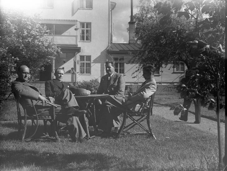 """Text till bilden: """"4 herrar vid trädgårdsmöbel""""."""